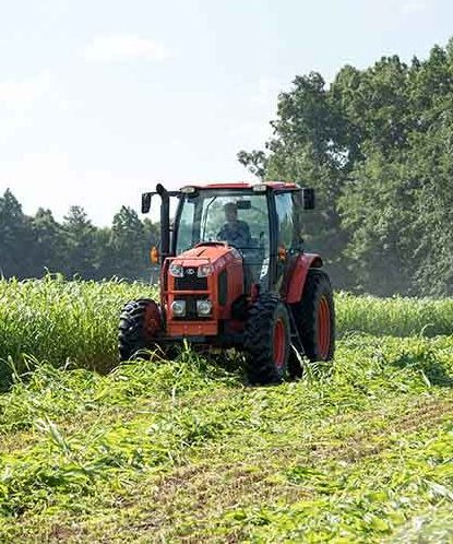 Red farm tractor plowing a field